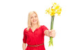 Woman handing out flowers towards the camera