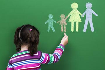 Girl drawing family holding hands on blackboard