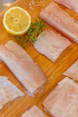 fresh raw fish slices with lemon on wooden cutting board
