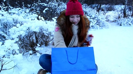 Lovely girl looks in surprise package, rejoices