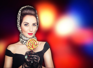Beautiful woman in retro pin up style with lollipop on the brigh