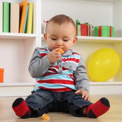 Baby beim Essen einer Mandarine Frucht