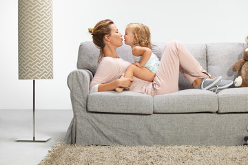 Young beautiful mother playing with daughter in livingroom