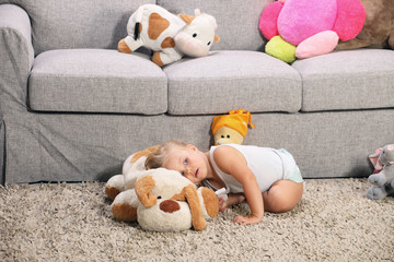 Young blonde girl playing with soft toys in living room
