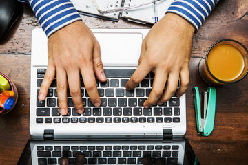 hands on the keyboard of a laptop on the desk work