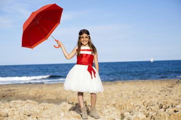 Niña con paraguas rojo en la playa
