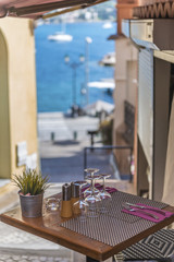 Restaurant table outside in a narrow street with a view of the h