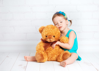 baby girl hugging a loved teddy bear
