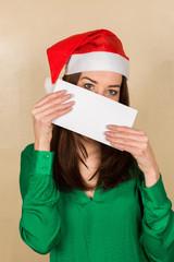 Junge Dame mit Weihnachtsmann-Mütze hält leeres Schild