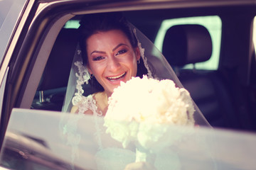 Bride laughing in the car