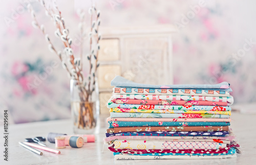 Leinwanddruck Bild Fabric Pile of colorful folded textile with sew items