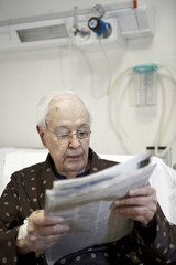 Elderly man reading the newspaper, in a hospital room