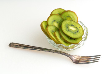 Bowl of kiwi with fork in front of bowl