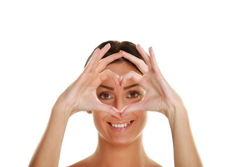 Portrait of beautiful young woman making heart shape by hands