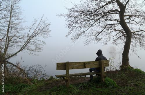 Fototapeta Depressed man sitting on a bench at a lake.