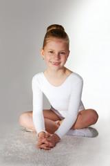 Children sport. Little sporty girl sitting on the  carpet over g