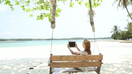 Young woman on beach using a digital tablet