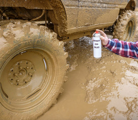 Aerosol spray on mud next off-road muddy SUV