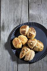 Vier brötchen, Sesam, Kübiskerne, Leinsamen, Käse, auf Holz