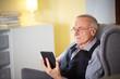 Senior man at home reading on a e-book 5