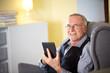 Senior man at home reading on a e-book 3
