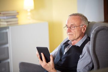 Senior man at home reading on a e-book 5
