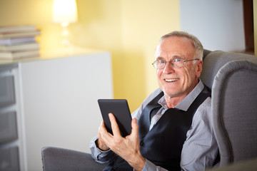 Senior man at home reading on a e-book 3