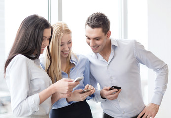 smiling business team with smartphones in office