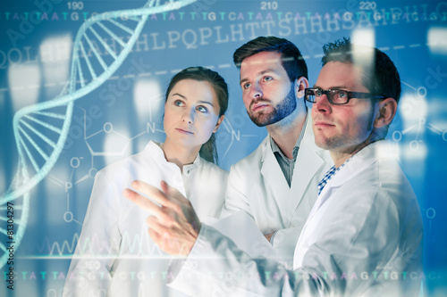 Leinwanddruck Bild Group of geneticists working at media screen
