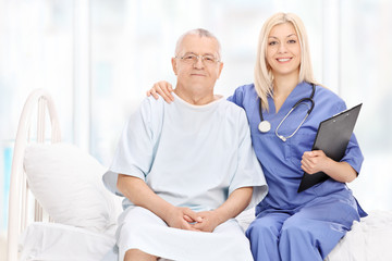 Female doctor and a mature patient seated on bed
