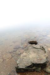 scoglio di lago nella nebbia