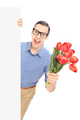 Man holding bunch of red tulips behind a panel