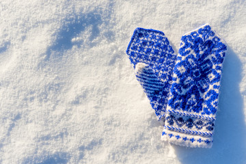 warm woolen mittens with beautiful pattern lying in the snow