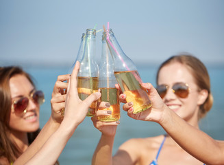 close up of happy young women with drinks on beach