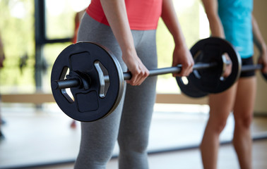group of women with barbells working out in gym