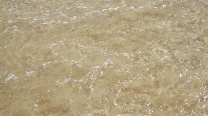 calm sea waves with sand close up