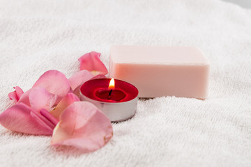 light pink rose,soap with tea light candle on white towel