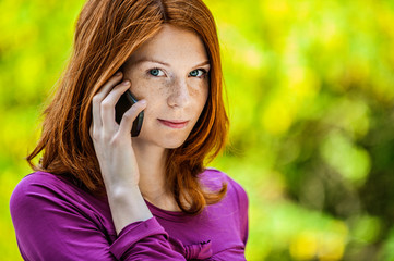 red-haired smiling young woman talking on phone