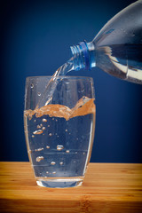 Water pouring into glass against blue background