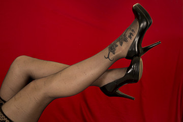 woman legs with tattoo on foot in black stockings on red in heel