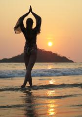 Young woman meditating on Palolem beach. South Goa, India