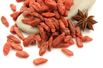 Goji berries on bright rock with star anise isolated