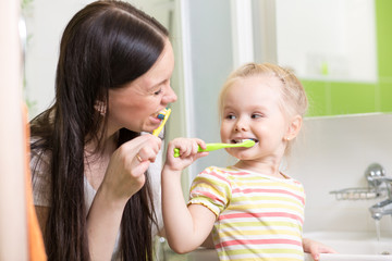 cute mom teaching child teeth brushing