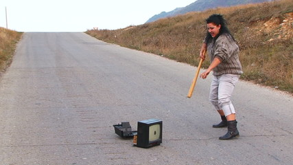 Mad Woman With Club Smashing a TV-set At Road