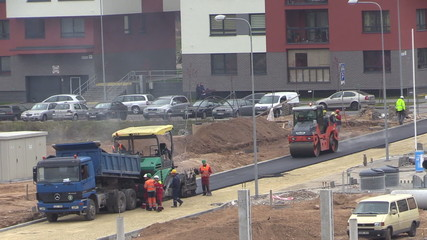 Workers pavers work with asphalt spreader and roller machines