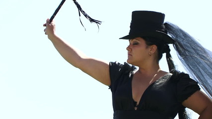 Woman In Black Swinging A Whip