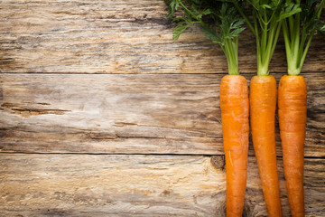 Fresh carrots on the wooden background.