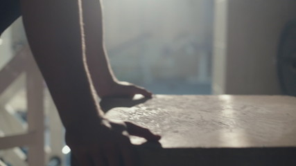 Close-up of man jumps on the wooden cube in the gym
