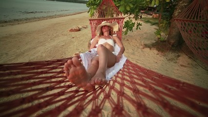 Woman on vacation relaxing on hammock at sunset