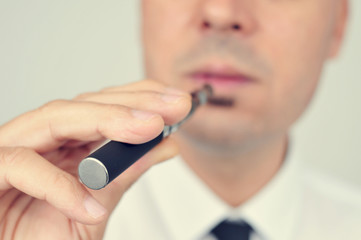 young man vaping with an electronic cigarette